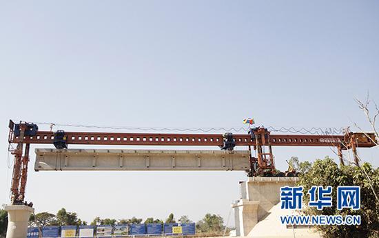 这是2月9日在老挝首都万象拍摄的楠科内河特大桥架梁施工现场。新华社发(臧衡 摄)
