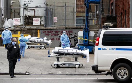 医护人员将物化亡患者迁移至一时停尸房(图源:纽约时报)