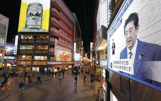 4月7日,在日本大阪,电子表现屏正在播放日本始相安倍晋三发布危险事态宣言的消息。新华社/共同社