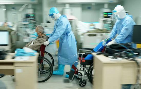 武汉火神山医院重症医学一科副主任宋立强(中)护送81岁新冠肺炎重症患者去做CT检查