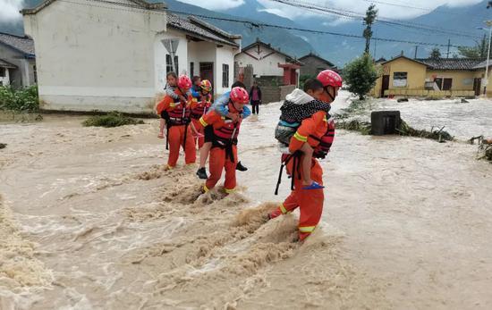 6月27日,四川省凉山彝族自治州冕宁县境内显现强降雨天气,消防声援人员在洪水中迁移儿童。