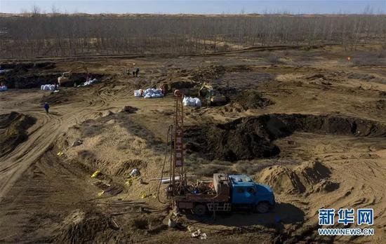 """11月13日,工人在""""美利林区""""清理污染物(图源:新华社)"""