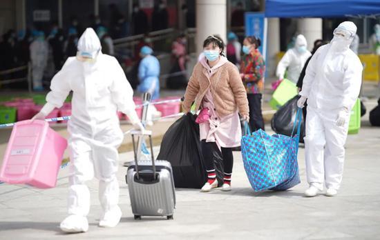 武汉江夏方舱医院,医护人员帮助新冠肺炎治愈患者(中)拿行李
