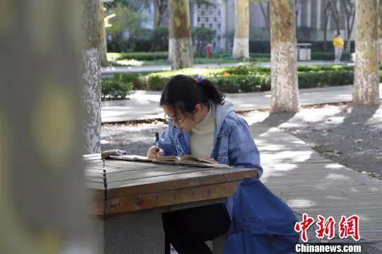 图为山东大学文学院2018级硕士研究生丁安琪在山东大学小树林晨读。来源:中国新闻网 (孙宏瑗 摄)
