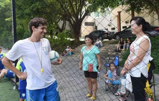 资料图:一名外教与学生家长进行交流。新华社记者 卢汉欣 摄