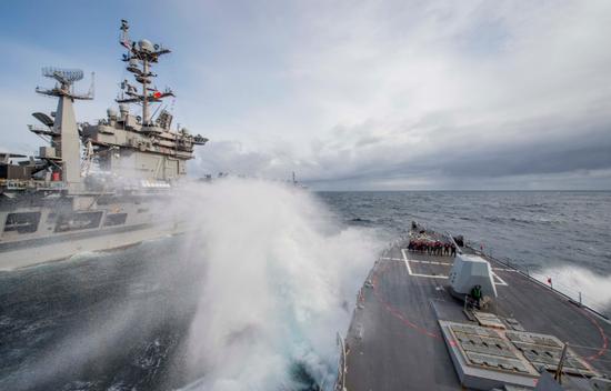 """2018年9月19日,阿利伯克级导弹驱逐舰法拉古号(DDG 99)与尼米兹级航空母舰""""杜鲁门""""号(CVN 75)在海上进走补给。""""杜鲁门""""回去以后,法拉格特现在仍在美国第6舰队辖区战备执勤"""