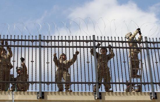 美国德克萨斯州麦卡伦美墨边境附近,美军士兵正在安装带电铁丝网。(图源:路透社)