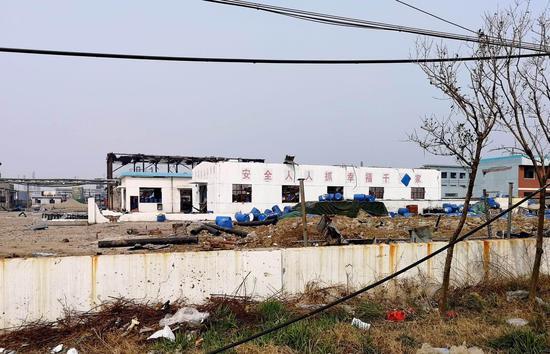 响水县生态化工园内,一家工厂在爆炸事故中受损严重,墙体上的安全标语惹人注目。