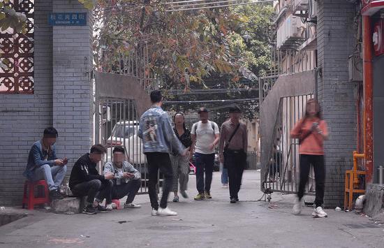 3月16日下午,广州市白云世界皮具贸易中心旁桂花岗小区。记者连续多日观察后发现,该小区的几个入口和内部,长期有拉客人员和望风看场子的人员聚集。    新京报记者 吴江 摄