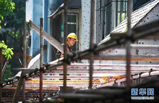 4月26日,工人在重庆市渝中区大溪沟街道双钢路社区改造提升项目施工现场作业。 新华社记者 王全超 摄