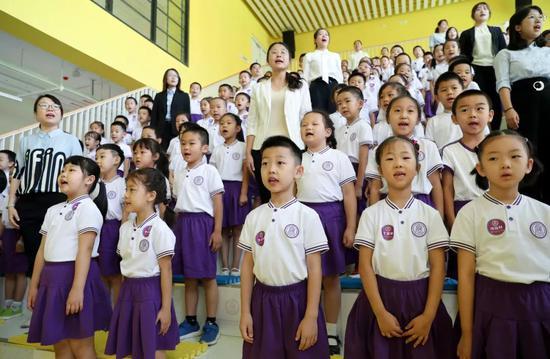 2019年9月1日,新成立的清华大学附属中学广华学校小学部首批152名一年级新生和老师在开学典礼上高唱国歌。图片来源:新华社
