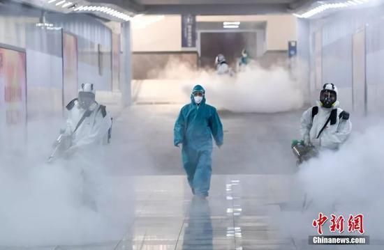 资料图:十余位来自长沙蓝天救援队的志愿者手持重型消毒机器,对长沙火车站内外进行消毒杀菌。中新社记者 杨华峰 摄