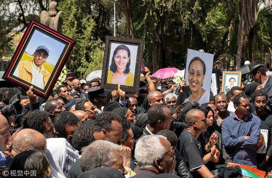 親屬們舉著遇難者的肖像。