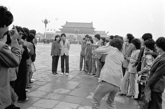 1987年5月1日,辽宁省丹东汽车制造厂23对新婚夫妇在北京天安门广场冒着蒙蒙细雨拍照纪念。他们是在厂里参与集体婚礼后来北京旅游的,旅游结婚开端在当时的年轻人中盛行。 本文图片均为新华社 材料图