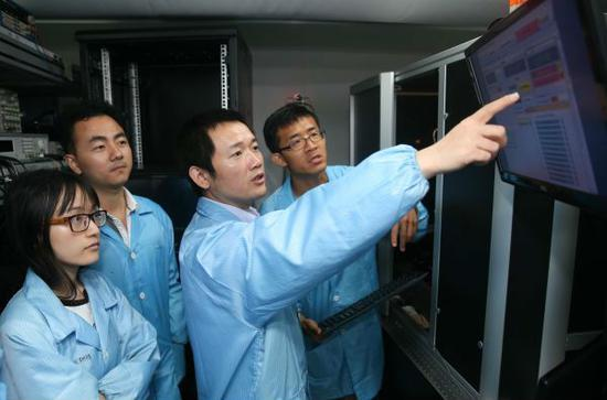 5月15日,在上海交通大学,金贤敏教授(右二)在实验室请示弟子熟识光量子芯片制备的要点。(新华社)