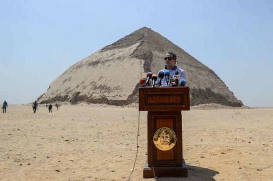 """埃及文物部长哈立德·阿纳尼站在""""弯曲""""的金字塔前发表讲话。(法新社)"""