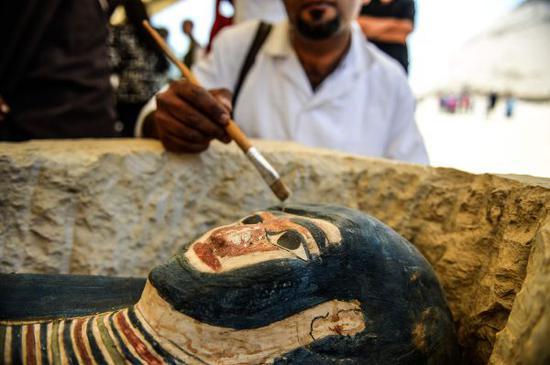 工作人员正在清理从金字塔中发现的木乃伊。(法新社)