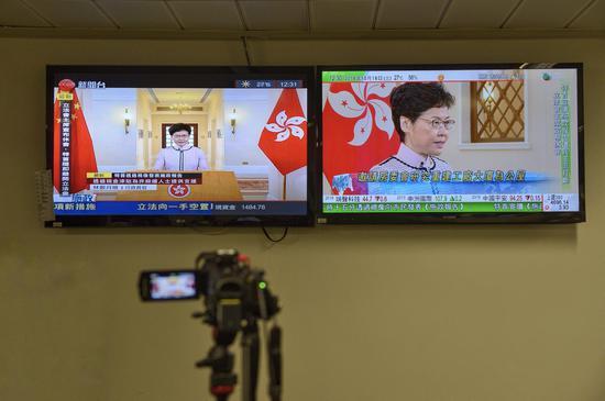 立法会大楼媒体厅内,电视在播放林郑月娥宣读施政报告的内容。新京报特派香港报道组摄