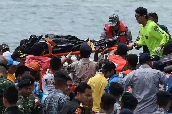 7月6日,在泰国普吉岛差隆码头,救援人员搬运一名遇难者遗体。新华社/法新