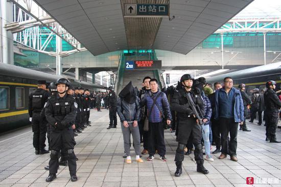 ▲警方将嫌疑人从重庆押解回广元