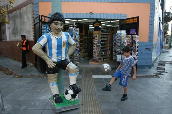 博卡区别名孩子在马拉多纳雕塑旁踢足球