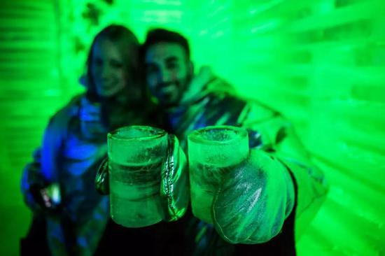 """在卡拉法特市冰川博物馆,游客在用莫雷诺冰川浮冰构建的""""冰川酒吧""""里展现冰杯"""