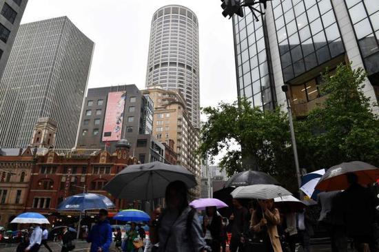 2018年11月28日,在澳大利亚悉尼,走人撑伞前走。(新华/法新)