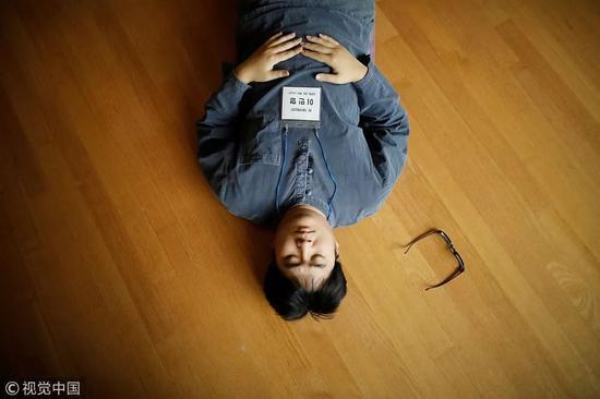 """△ 2018年11月10日,在被关进""""牢房""""之前,一名参与者躺在地板上冥想。"""