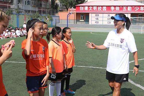 中国女足前国脚张欧影给中美青少年进走足球培训。