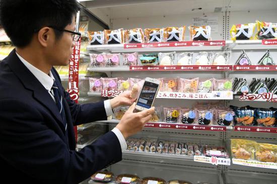 4月23日,在日本东京罗森集团一家便利店,做事人员演示手机自立扫码结帐。