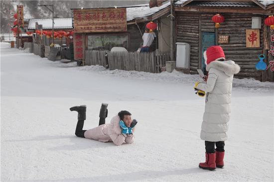 雪乡景区内,游客在拍照游玩。