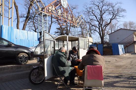 12月17日,原北京游笑园南门,大门已经被封挡,几位老人在晒太阳打牌。新京报记者 王贵彬 摄