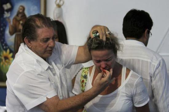 巴西灵媒师约翰(左)为患者治疗。