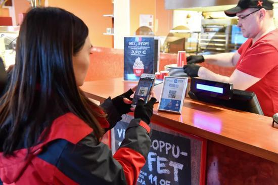 ▲资料图片:2018年1月19日,在芬兰罗瓦涅米,一名中国游客在一家酒店使用支付宝二维码支付餐费。(新华社发)