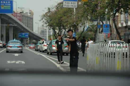 3月17日下午,广州市白云世界皮具贸易中心门前的解放北路,一名拉客人员在机动车道上往一辆私家车内递名片。 新京报记者 吴江 摄