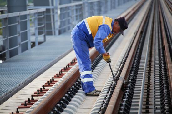 ▲中铁大桥局中俄同江铁路大桥项目的建设者正在对钢轨精度进行微调。(6月4日摄)本报记者谢锐佳摄