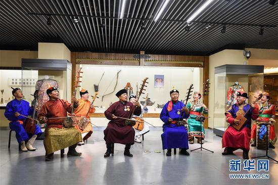 7月15日,在赤峰博物馆,《格萨(斯)尔》国家级非遗传承人金巴扎木苏(前排右二)和团队一起表演节目。新华社记者 刘磊 摄