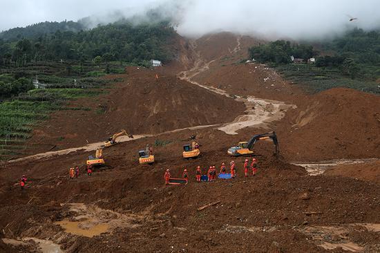 救援人員在山體滑坡現場開展救援。
