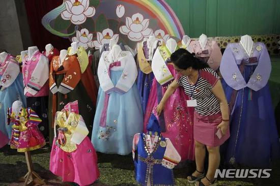 ▲一位女士在选看朝鲜服(纽西斯通讯社)