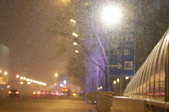 东单北大街雪花纷飞。宋佳音 摄