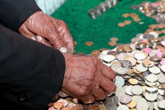 吴锦泉在江苏省南通市红十字会清点硬币,为四川雅安地震灾区捐款。(新华社)