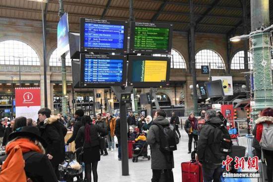 当地时间12月22日,民众在法国主要交通枢纽巴黎北站查看火车时刻表。当天法国国家铁路公司(SNCF)只提供很有限的客运列车服务。圣诞假期已经来临,但大罢工仍然持续,导致民众出行困难。SNCF呼吁民众取消或更改出行计划。中新社 记者 李洋 摄