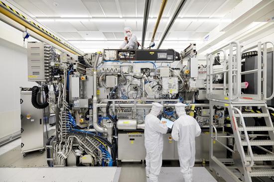 ASML公司员工正组装一台半导体光刻机 图自:路透社 下同