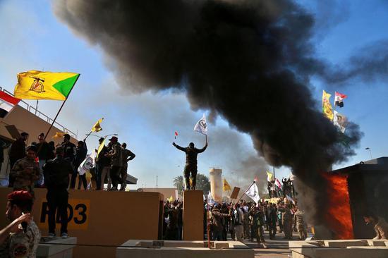 2019年12月3日,抗议者在美国驻巴格达大使馆前点火焚烧房屋。图据美联社