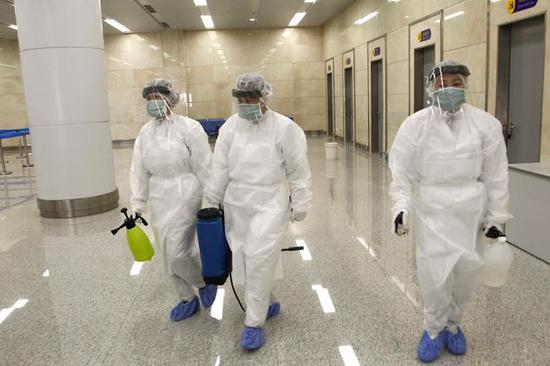 带着防护装备和消毒剂的官员准备在平壤国际机场检查从国外入境旅客的健康状况 图自美媒