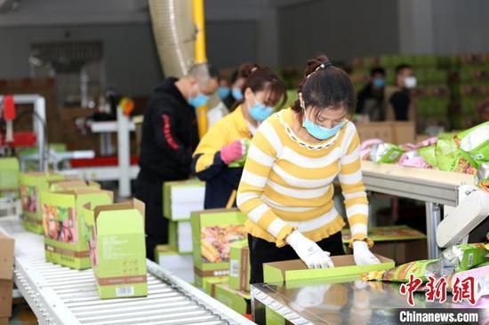 原料图:工人与自觉者正在螺蛳粉生产线上忙碌。 朱柳融 摄