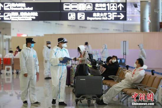 3月16日,身着防护服的公安民警在江苏省南京市禄口国际机场对入境旅客开展新冠肺炎疫情防控工作。中新社记者 泱波 摄