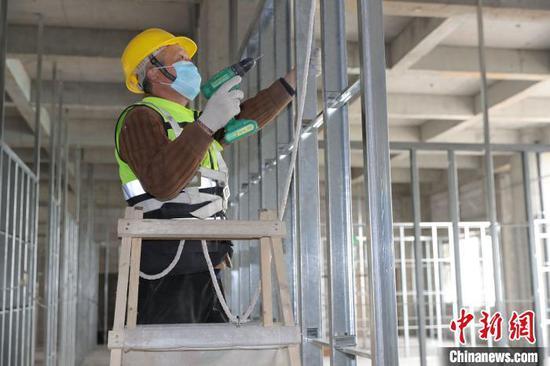 图为工人戴口罩施工。 苏鲲 摄