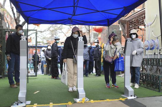 校门口安放了三个测温仪,家长进入前都要测量体温。摄影/新京报记者 浦峰