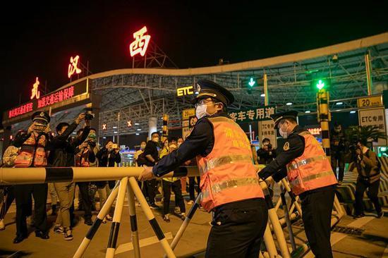 4月8日凌晨,在武汉西高速收费站,工作人员移除围栏。澎湃新闻记者 孙湛 图